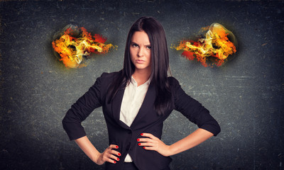 Angry woman standing with arms akimbo, fire from ears. Concrete
