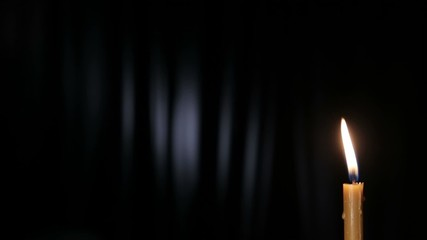 A wax candle burning on a black background.
