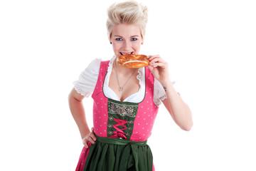 Junge Frau im Dirndl isst Breze und lächelt freundlich