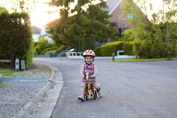 Toddler girl driving wooden tricycle on the street