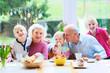 Leinwandbild Motiv Grandparents with grandchildren enjoying Easter breakfast