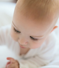 Portrait of a cute baby with gorgeous long eyelashes looking dow
