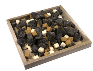 An assortment of liquorice candies on a wooden plate over white