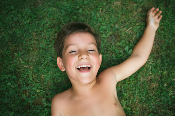 Portrait of a cute 5 year old boy lying on the grass with one ar