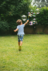 Cute 5 year old boy running making soap bubbles