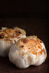 Roasted garlic heads on rustic surface