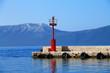 Red lighthouse in small mediterranean town Gradac , Croatia