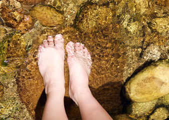 Pair of female feet standing in a stream