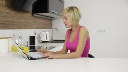 young woman typing keyboard laptop sitting at table kitchen home