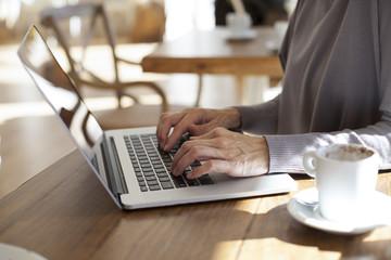 typing laptop in cafe horizontal