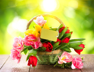Basket of spring holiday flowers with greeting card