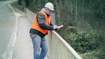 Engineer writing documentation on the bridge