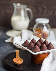 Candy chocolate truffles, cream jug and a cup of coffee