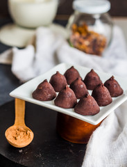 chocolate truffles, cocoa powder in a wooden spoon