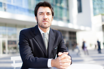 Handsome businessman sitting at a table outdoor