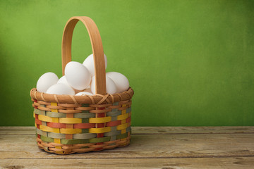 Eggs in basket on wooden table over green background
