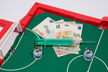 Figures of footbal players on euro banknotes,  syringe