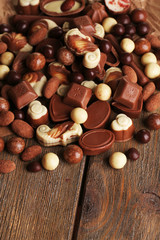 Different kinds of chocolates on wooden table close-up