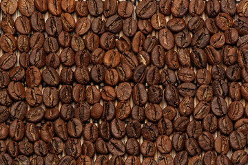 Roasted coffee beans laying on a straw mat with extended DOF
