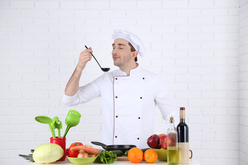 Chef at table with different products and utensil in kitchen