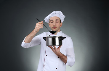 Chef with saucepan and ladle in hands on dark background