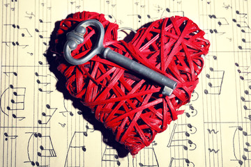 Retro key with wicker heart on music book background