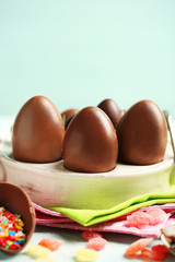 Chocolate Easter eggs on plate, on color wooden background