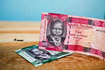 One and five Pound  Banknote from South Sudan on wood backgroun
