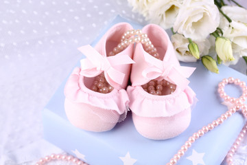 Pink baby boots with gift close-up
