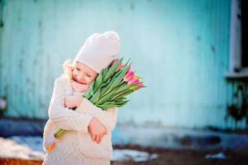 happy child girl with bouquet of tulips in early spring