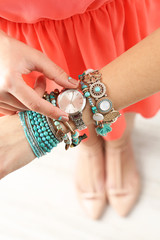 Stylish bracelets and clock on female hand top view