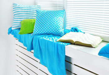 Colorful pillows and book on windowsill