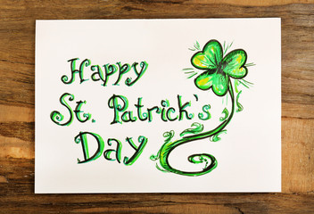 Greeting card for Saint Patrick's Day on wooden table