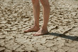 Leinwandbild Motiv feet on the cracked dry ground