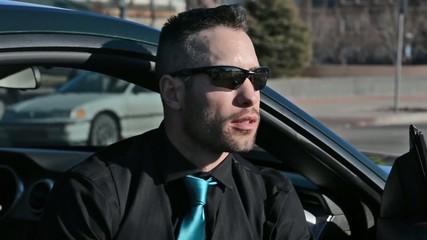 A handsome man waiting near his car