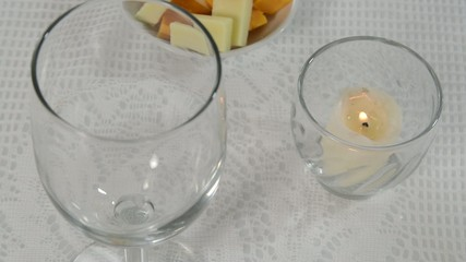 Setting a table with a wine glass and a burning candle