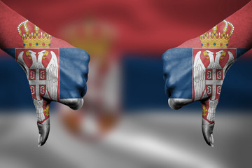 failure of Serbia - hands gesturing thumbs down in front of flag