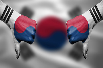 failure of  South Korea - hands gesturing thumbs down in front o