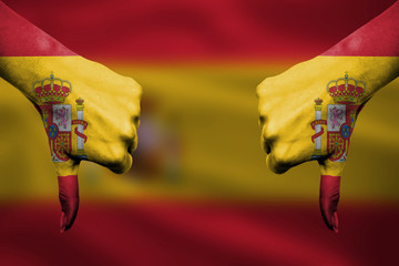 failure of Spain - hands gesturing thumbs down in front of flag