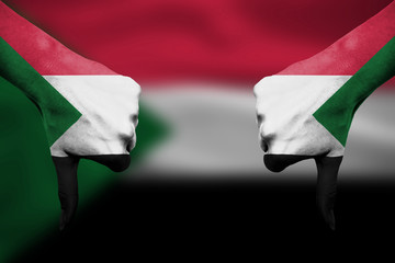 failure of Sudan - hands gesturing thumbs down in front of flag
