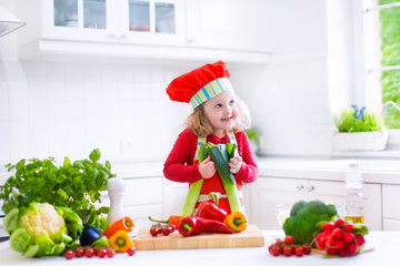 Little girl making salad for dinner