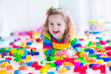Little girl playing with toy blocks