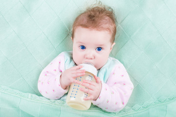 Sweet baby with big blue eyes drinking milk