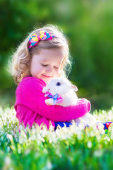Beautiful little girl playing with a rabbit