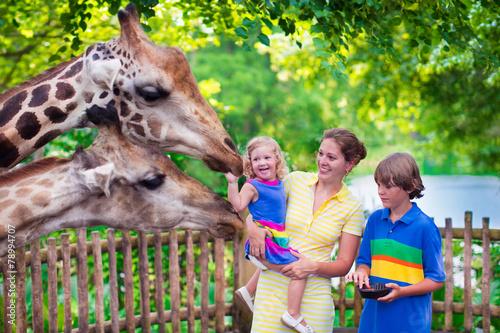 Leinwanddruck Bild Family feeding giraffe in a zoo
