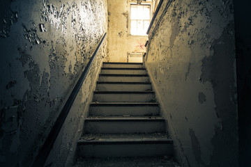 Dark  staircase with bright window in abandoned home