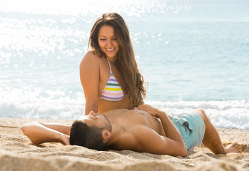 Smiling pair laying on sand beach