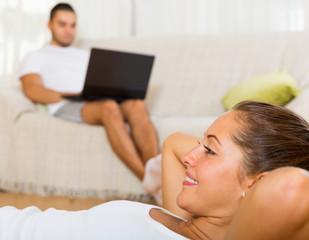 woman training on mat and inert boyfriend resting