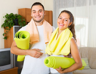 Smiling couple with towels before yoga class