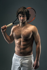 Male with naked torso and tennis racket.
